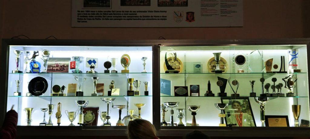 Vitrina de trofeos e mural cos logros do Sal Lence / SABELA MOSCOSO