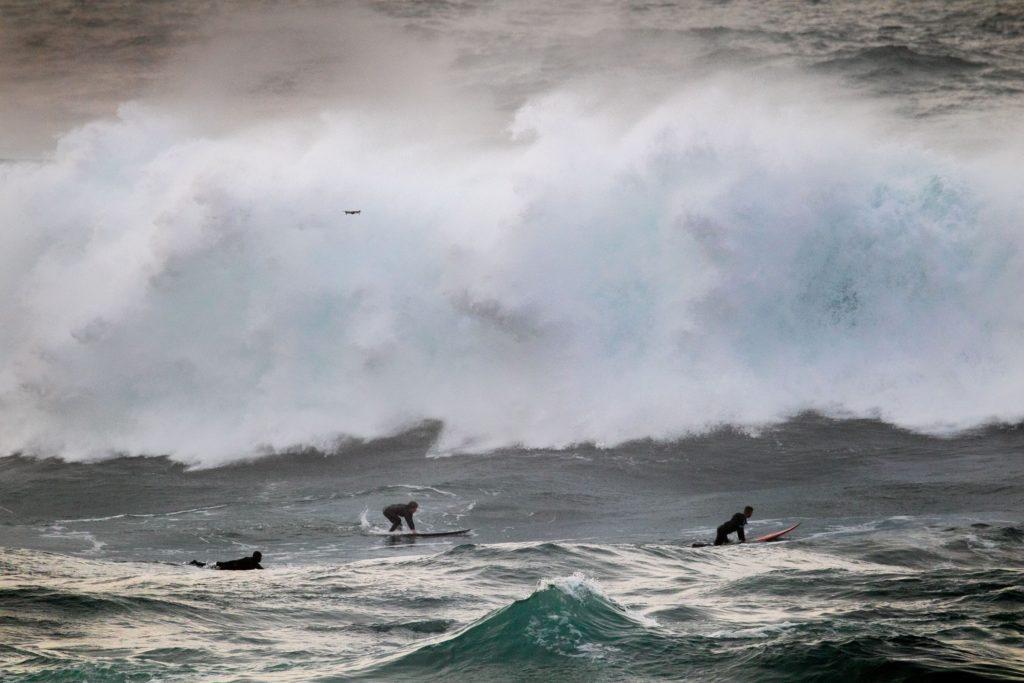 Foto dos tres locais na escuma, nesta imaxe pódense ver os tres surfistas a piques de ser engulidos pola onda / DANIEL ALMEIDA