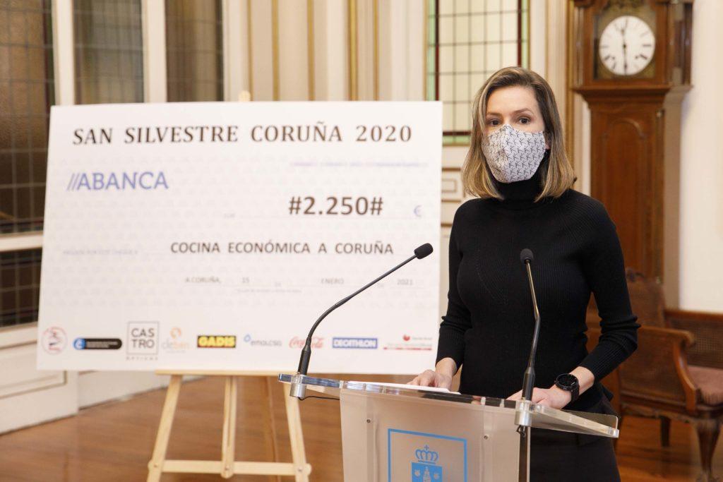 Entrega por parte da concelleira de Deportes, Mónica Martínez, do cheque co recadado na carreira San Silvestre á Cociña Económica / CONCELLO DA CORUÑA